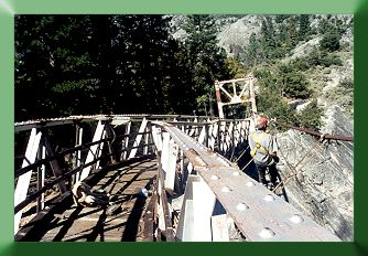 Looking down bridge centerline, showing bent top chord and Keith Monohan installing temporary suspenders.